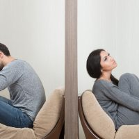 34842907 - conflict between man and woman sitting on either side of a wall